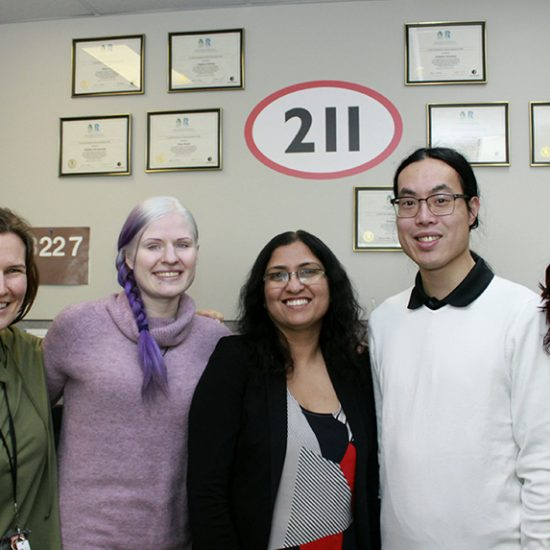 211 CRD Team in the Contact Centre with 211 logo on the wall in the background