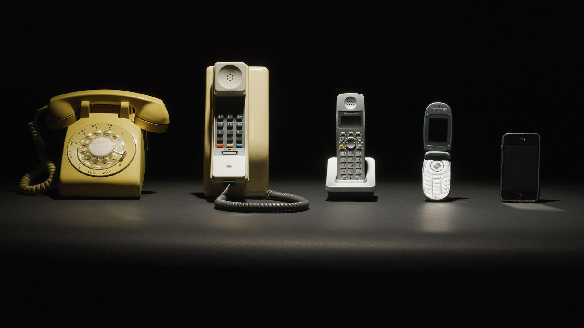 img des: Five phones on a flat surface, each from a different time period to represent five decades.