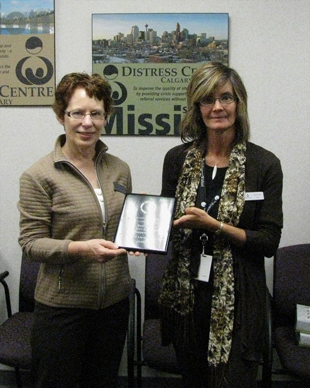 A woman presenting a plaque to another woman.