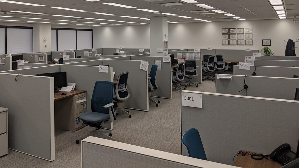 img description: A large empty room filled with cubicles and chairs.