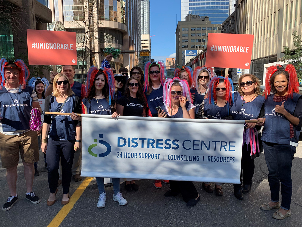 Distress Centre staff holding signs and a banner with the DC logo on it