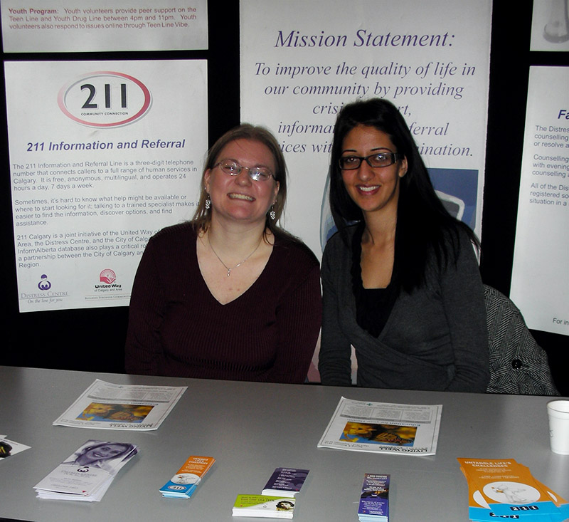 img des: Two people sitting at a table with brochures and a 211 sign behind them.