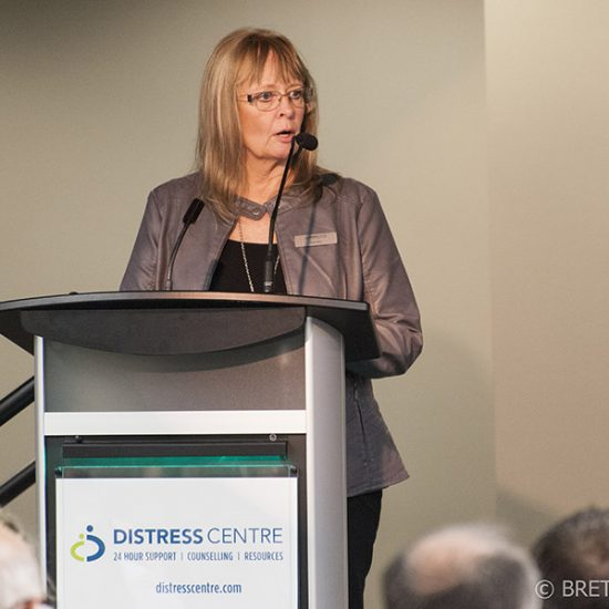 img des: Joan Roy speaking at a podium that has a Distress Centre sign on it.