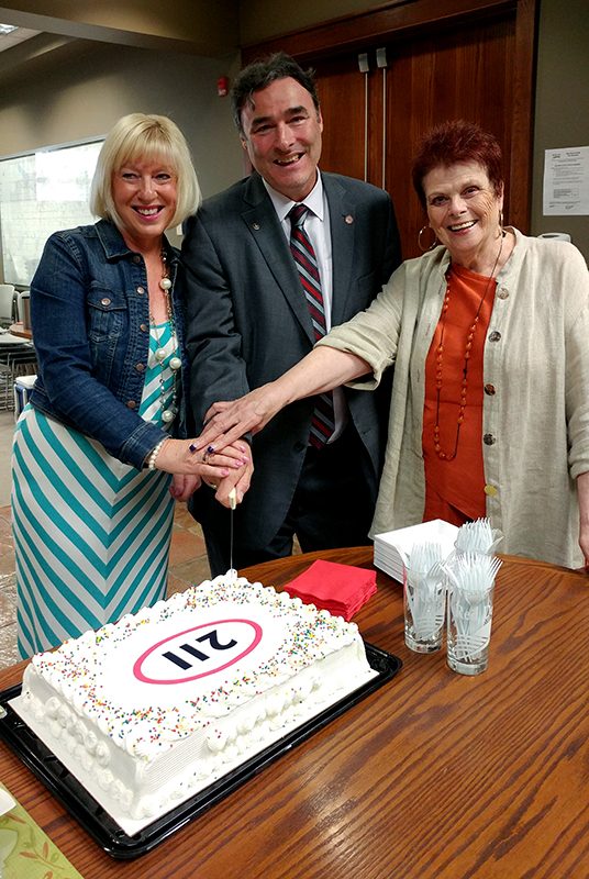 img des: Three people holding a knife over a cake that has the 211 logo.