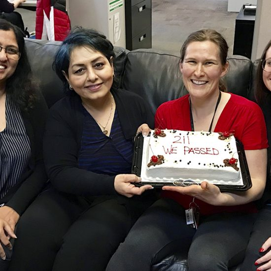 """img des: Four people sitting on a couch holding a cake that says """"we passed!"""""""
