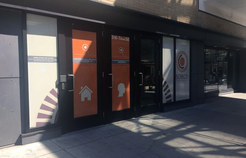 img des: The outside of SORCe, showing glass walls with orange and white coverings showing the SORCe logo, icons of a house and a person and text.