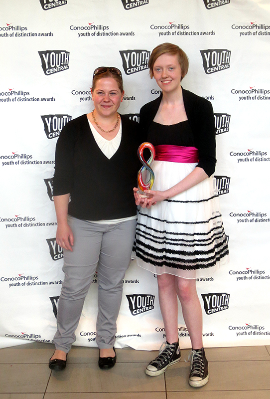 img des: Two people standing. One is holding an award.