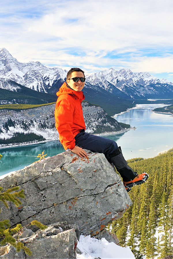 img des: Mark Li sitting on a rock with some mountains in the background
