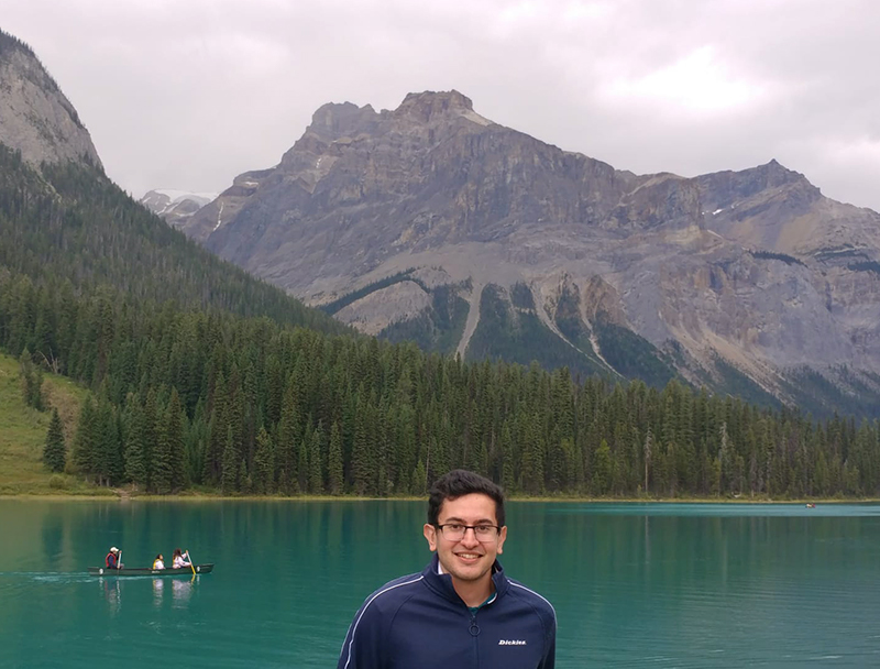 img des: Mortaza in the foreground, standing in front of Emerald Lake, with mountains in the background